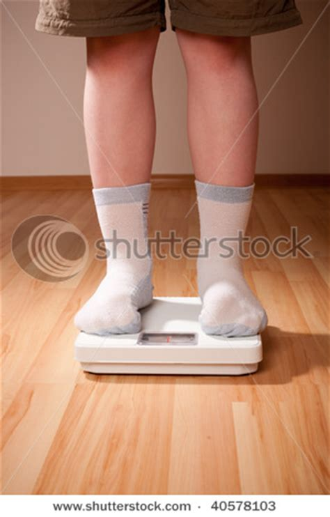 Picture of a Child, a Boy, Weighing Himself on a Scale
